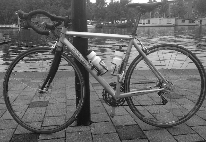 Racefiets tegen lantaarnpaal aan de Amstel