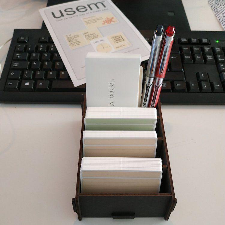 Kaartenbakje met kaartjes, pennen en envelopjes op bureau