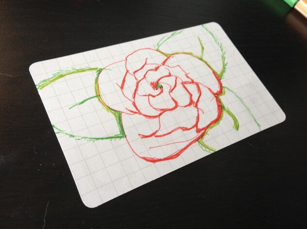 Little drawing of a red rose on a usem note card